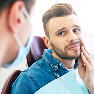 A male patient holding his cheek in pain while looking at the dentist