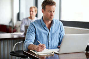 man looking and dental insurance plan on laptop