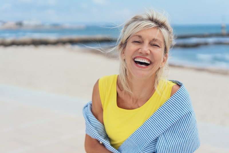 an older woman standing on the beach and showing off her new dental implants